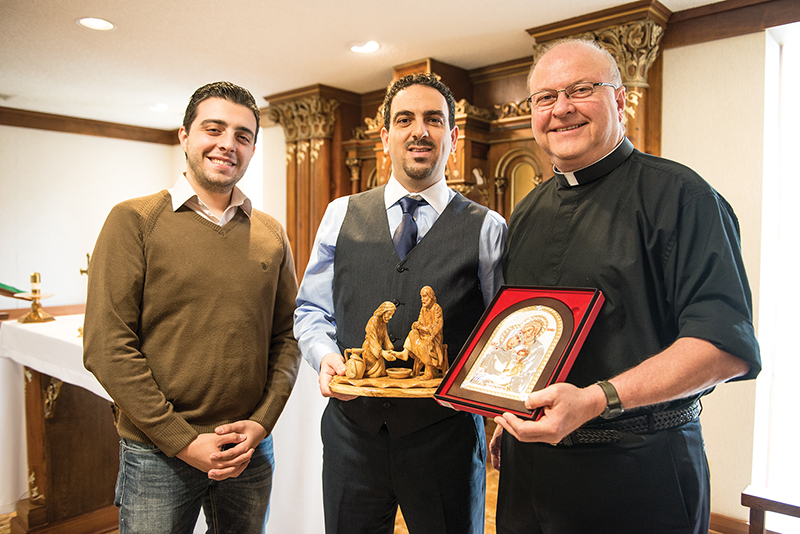 Elias Jabbour (left) and Awad Qumseya, Omaha-based sales representatives of Blest Art, meet with archdiocesan vicar general Father Gary Pennings at Savior Pastoral Center in Kansas City, Kansas. Blest Art has been authorized by the archdiocese to visit parishes and offer heirloom-quality, olive wood carvings made by Christians in the Holy Land. Sales of this art is one of the few sources of income for the shrinking Christian population. Leaven photo by Joe Bollig