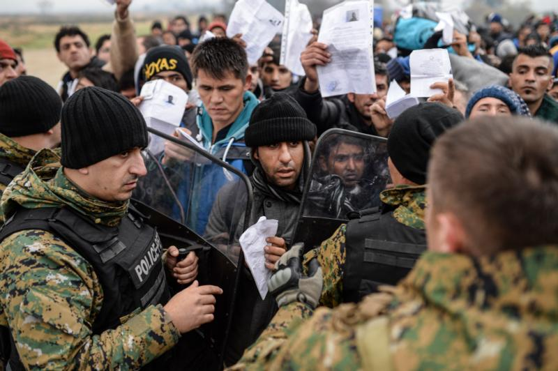 "Migrants and refugees show their ID papers to Macedonian police Nov. 20 and wait to cross the Greek-Macedonian border near Gevegelija, Macedonia. The extensive vetting process that all refugees undergo before arriving in the United States, ""screens out any possible threat of terrorism,"" said the executive director of the U.S. bishops' Migration and Refugee Services. (CNS photo/Georgi Licovski, EPA)"