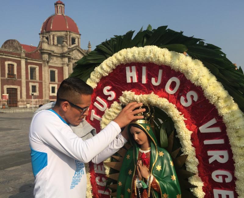 Un hombre ajusta la corona de una estatua de Nuestra Señora de Guadalupe el 6 de diciembre frente a la basílica que lleva el nombre de ella en el norte de Ciudad de México. La santa patrona nacional sigue siendo importante en México como fuente de inspiración espiritual, pero hasta personas no religiosas se identifican con ella. (Foto CNS-David Agren)