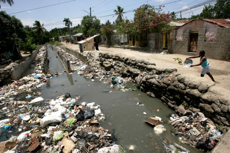 "Pope Francis emphasized protection for the environment and the need to mitigate climate change in his second encyclical, ""Laudato Si',"" released in June. In this June 6, 2009, photo a woman throws rubbish into a stream that crosses the neighborhood La Cienaga, Dominican Republic. (CNS photo/Orlando Barria, EPA)"