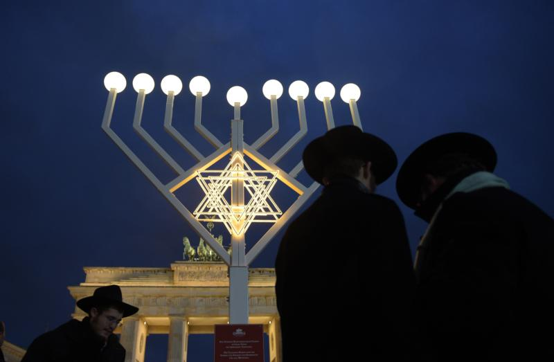 """An illuminated Hanukkah menorah stands in front of the Brandenburg Gate in Berlin in this Dec. 23, 2014, file photo. Although Catholic are called to witness to their faith, the church """"neither conducts nor supports"""" any institutional missionary initiative directed toward Jews, according to a new document from a Vatican commission. (CNS photo/Rainer Jensen, EPA)"""