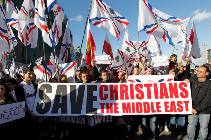 Assyrian Christians, who had fled Syria and Iraq, carry placards and wave Assyrian flags during a gathering in late May in front of U.N. headquarters in Beirut. (CNS photo/Nabil Mounzer, EPA)