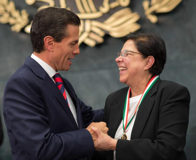 Mexican President Enrique Pena Nieto congratulates Sister Consuelo Morales, a member of the Congregation of Our Lady: Canonesses of St. Augustine, after presenting her with Mexico's national human rights award Dec. 10 in Mexico City for her work with the families of disappeared persons. (CNS photo/Presidency of the Republic)