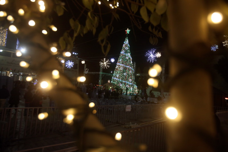 People attend the lighting of the Christmas tree on Manger Square in Bethlehem, West Bank, Dec. 5. Latin Patriarch Fouad Twal urged a more spiritual celebration of Christmas this year and called for an end to the arms trade. (CNS photo/Abed Al Hashlamoun, EPA)