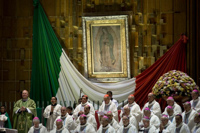 The original tilma of St. Juan Diego bearing the miraculous image of Mary is seen in the Basilica of Our Lady of Guadalupe in Mexico City in this Nov. 17, 2013, file photo. Pope Francis will venerate the original image of Our Lady of Guadalupe Feb. 13 during his six-day visit to Mexico. At left is Cardinal Timothy M. Dolan of New York, who was celebrating a Mass with other bishops. (CNS photo/David Maung)