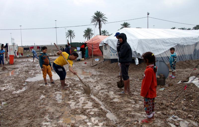 Young internally displaced Iraqis try to dig a drainage trench after heavy rains in early November at a camp in Baghdad. (CNS photo/Ahmed Jalil, EPA)