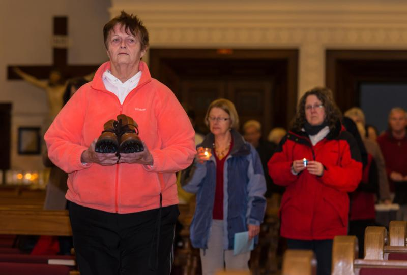 Participants at the seventh annual Greater Green Bay Area Homeless Persons' Interfaith Memorial Service, held Dec. 21 at St. John the Evangelist Church in Green Bay, Wis., join in a procession carrying shoes and candles representing homeless men and women who died in 2015. (CNS photo/Sam Lucero, The Compass)