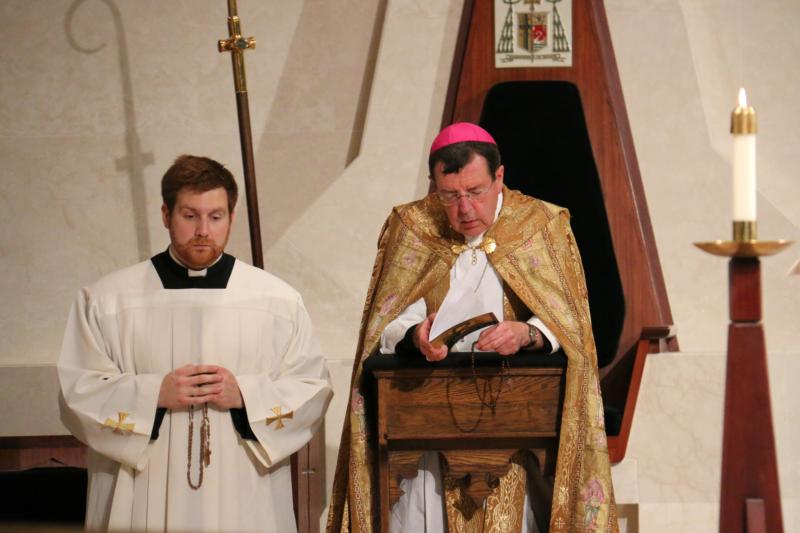 Detroit Archbishop Allen H. Vigneron and Father Stephen Pullis kneel to pray the rosary during a special prayer service in late November for Christians in the Middle East at the Cathedral of the Most Blessed Sacrament. (CNS photo/Jonathan Francis, Archdiocese of Detroit)