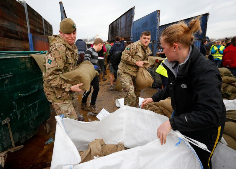 Local volunteers and the British Army fill sandbags Dec. 28 to stem floodwater in York, England. Pope Francis called on Christians to pray for victims of several natural disasters that have hit parts of the United States, Great Britain and Paraguay. (CNS photo/Lindsey Parnaby, EPA)