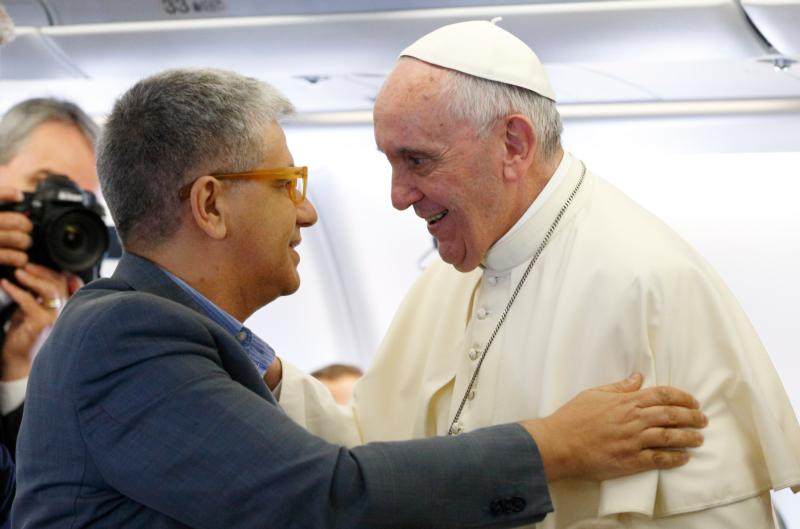 "Pope Francis greets Italian journalist Andrea Tornielli aboard his flight from Rome to Quito, Ecuador, in this July 5, 2015, file photo. Tornielli conducted an interview with the pope on the topic of mercy. The interview is contained in a new book titled, ""The Name of God Is Mercy."" (CNS photo/Paul Haring)"