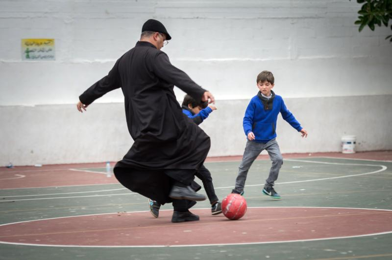 A unidentified bishop plays soccer with boys during a Jan. 7 visit in Gaza City. The bishop was part of a delegation from North America, Europe and South Africa. (CNS photo/Marcin Mazur, Bishops' Conference of England and Wales)