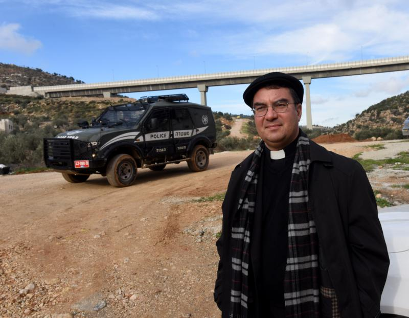 Bishop Oscar Cantu of Las Cruces, N.M., stands in front of an Israeli border police jeep Jan. 10 near the Palestinian land in the Cremisan Valley in Beit Jalla, West Bank. (CNS photo/Debbie Hill)
