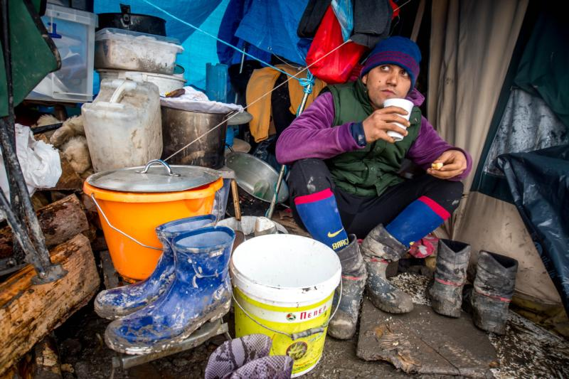 A refugee drinks tea in front of his tent in the refugee camp in the coastal town of Grande-Synthe near Dunkirk, France, Jan. 10. (CNS photo/Stephanie Lecocq, EPA)