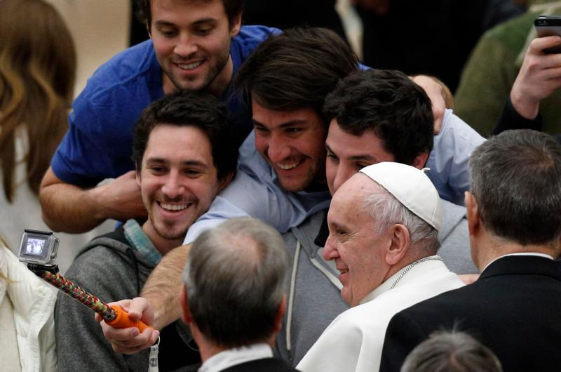 Young men take a selfie with Pope Francis as he leaves his general audience in Paul VI hall at the Vatican Jan. 20. (CNS photo/Paul Haring)