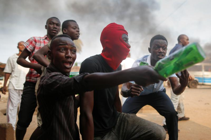 Burundian protesters react as they face off with police officers firing shots toward them during an anti-government demonstration in 2015 in Bujumbura, Burundi. A Catholic aid worker in Burundi says plans are now ready to evacuate staffers, but insists church-backed dialogue could still avert civil war. (CNS photo/Dai Kurokawa, EPA)