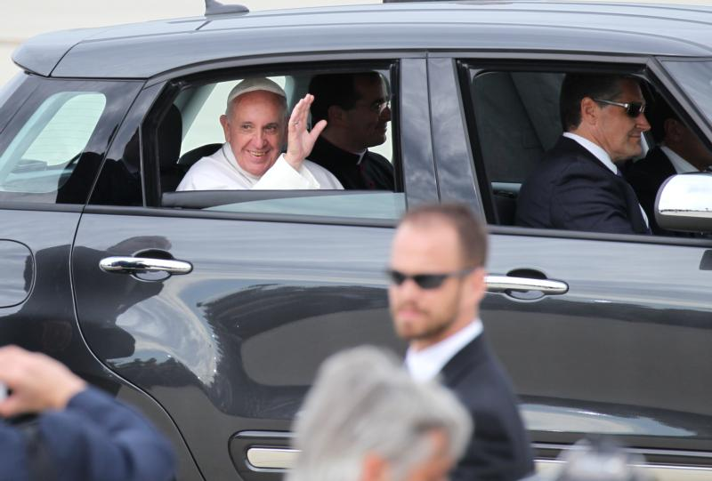Pope Francis waves from a Fiat 500 L sedan as he leaves the airfield at Joint Base Andrews in Maryland Sept. 22. The Archdiocese of Philadelphia is auctioning off two of the same model cars used to shuttle Pope Francis around the Philadelphia area during his visit to the city last September. (CNS photo/Bob Roller)