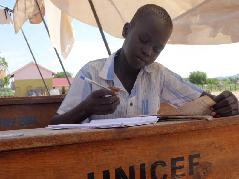A student at the Sant'Egidio School takes notes in 2015 during a break from class in Adjumani, Uganda. For the hundreds of South Sudanese refugee children settled into a Ugandan camp, learning how to react without violence is as much a part of their school work as academic pursuits.(CNS photo/courtesy Sister Grace Candiru)