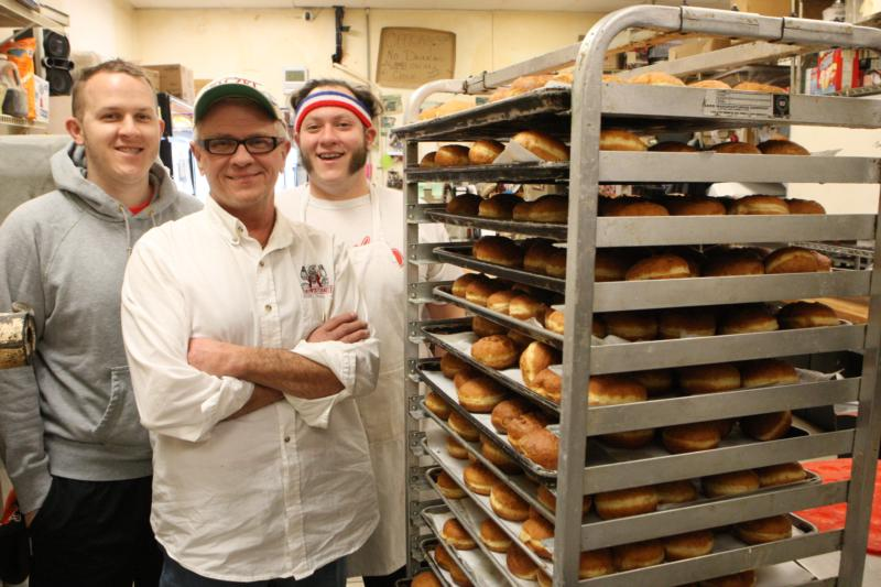 "Tim Kiedrowski, center, owner of Kiedrowski's Simply Delicious Bakery, with sons, Tim, left, and Michael, are shown Jan. 18 with a rack of Polish-style doughnuts, known as ""paczki."" The doughnuts are a tradition in the days before Lent. (CNS photo/Dennis Sadowski)"