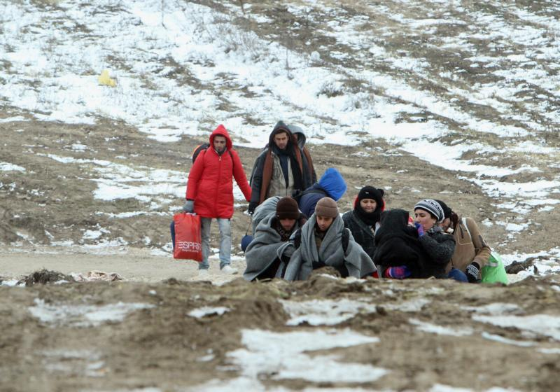 A group of migrants from Syria, Iraq and Afghanistan, on their way to seek asylum in Germany or Austria, walk Jan. 24 along the frozen route from the border between Serbia and Macedonia to a temporary camp for migrants. Catholic bishops in Germany and Austria urged their countries to continue accepting refugees, despite demands for new restrictions after New Year's Eve violence in Cologne and other cities. (CNS photo/Djordje Savic, EPA)