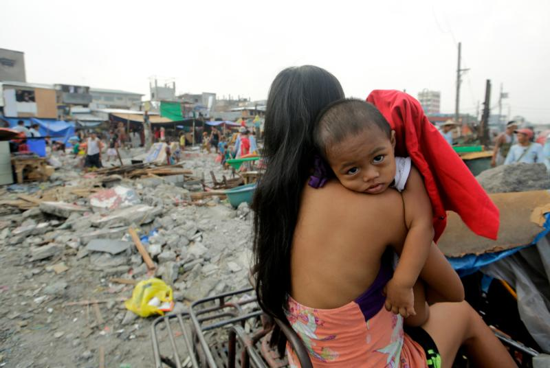 A mother holds her child while a demolition team tears down houses in 2014 during an eviction of illegal settlers in Manila, Philippines. Speakers at the 51st International Eucharistic Congress in Cebu called on the faithful to remember to help the poor and suffering. (CNS photo/Ritchie B. Tongo, EPA)