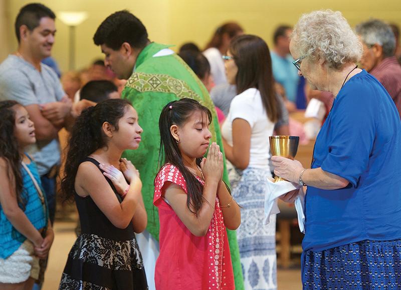 Leaven photo by Joe McSorley Angela Navarro distributes Communion at the Spanish-language Mass at Good Shepherd Parish in Shawnee. Hispanics make up 7.4 percent of Johnson County and eight percent of Johnson County Catholic elementary schools.