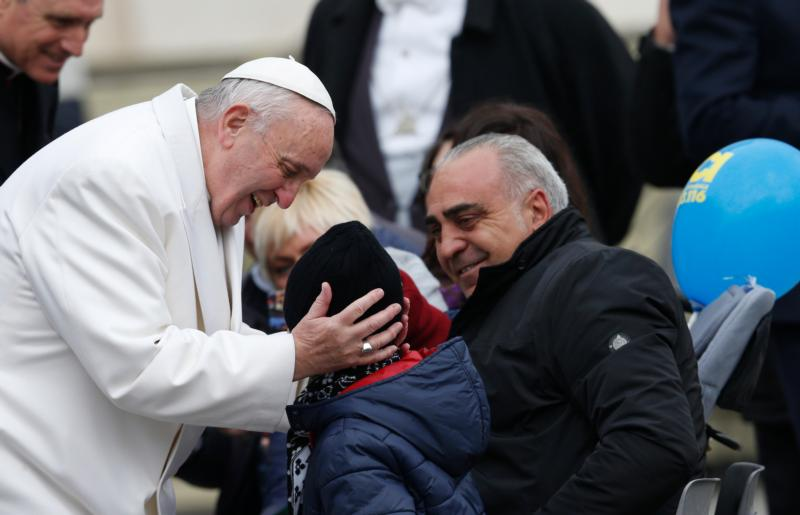 Pope Francis greets a child while meeting the disabled during a special audience for the Holy Year of Mercy in St. Peter's Square at the Vatican Jan. 30. (CNS photo/Paul Haring)