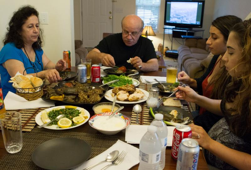 Iraqi refugee John Youkhanna and his family enjoy a traditional Middle Eastern meal at their home in Raleigh, N.C., Aug. 11, 2015. (CNS photo/Chaz Muth)
