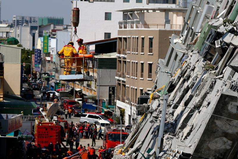 An earthquake survivor is seen on a crane Feb. 8 in Tainan City, Taiwan. Pope Francis sent condolences following the quake that hit as the island prepared to celebrate Chinese New Year.  (CNS photo/Ritchie B. Tongo, EPA)