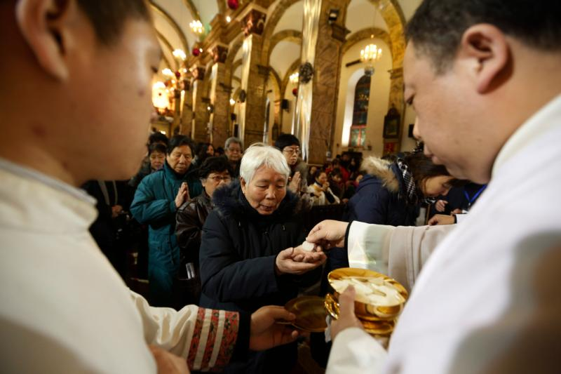 Chinese Catholics receive Communion in 2012 during Christmas Eve Mass in Beijing. A top Politburo official told faith leaders that religious groups must promote Chinese culture and become more compatible with socialism. (CNS photo/How Hwee Young, EPA)
