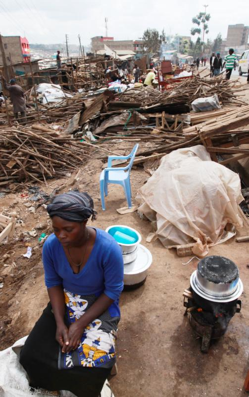A woman cooks outside her destroyed residence after hundreds of homes were demolished in 2015 during forced evictions in Nairobi, Kenya. The Kenyan bishops donated clothes and food to more than 4,000 households in the slums of Ngong after the launch of their national Lenten campaign. (CNS photo/Daniel Irungu, EPA)