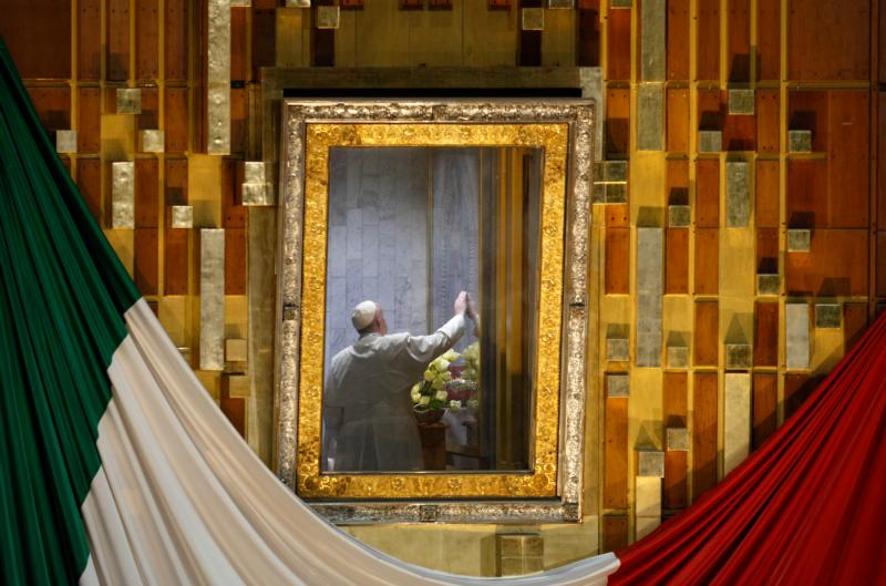"Pope Francis touches the original image of Our Lady of Guadalupe after celebrating Mass in the Basilica of Our Lady of Guadalupe in Mexico City Feb. 13. The Marian image was rotated for the pope to pray in the ""camarin"" (""little room"") behind the main altar. (CNS photo/Paul Haring)"