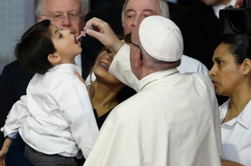 Pope Francis gives a vaccine to a boy held by Mexico's first lady Angelica Rivera during a visit to the Federico Gomez Children's Hospital of Mexico in Mexico City Feb. 14. (CNS photo/Paul Haring)