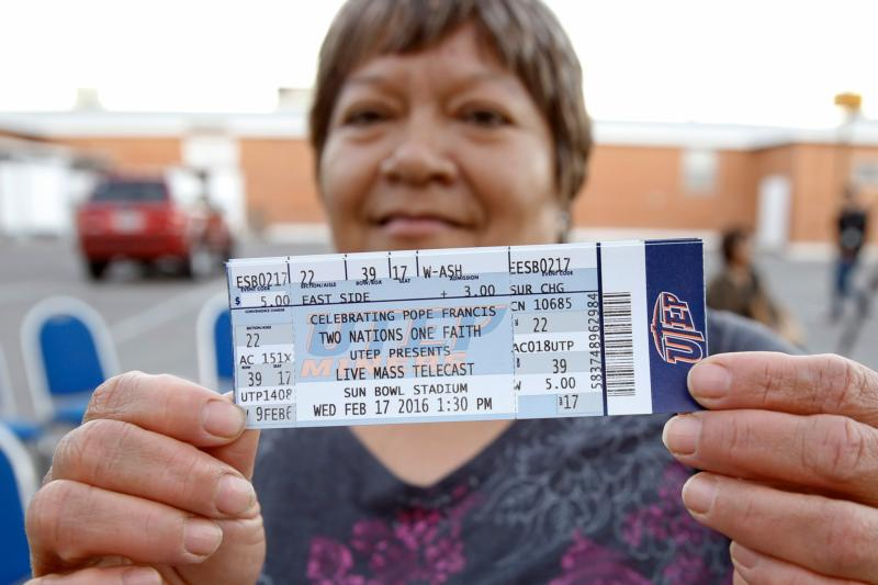 """A woman displays tickets to the Diocese of El Paso's """"Two Nations, One Faith"""" event Feb. 15 outside St. Ignatius Church in El Paso. The event coincides with Pope Francis' Feb. 17 visit to El Paso's sister city, Cuidad Juarez, Mexico. (CNS photo/Nancy Wiechec)"""