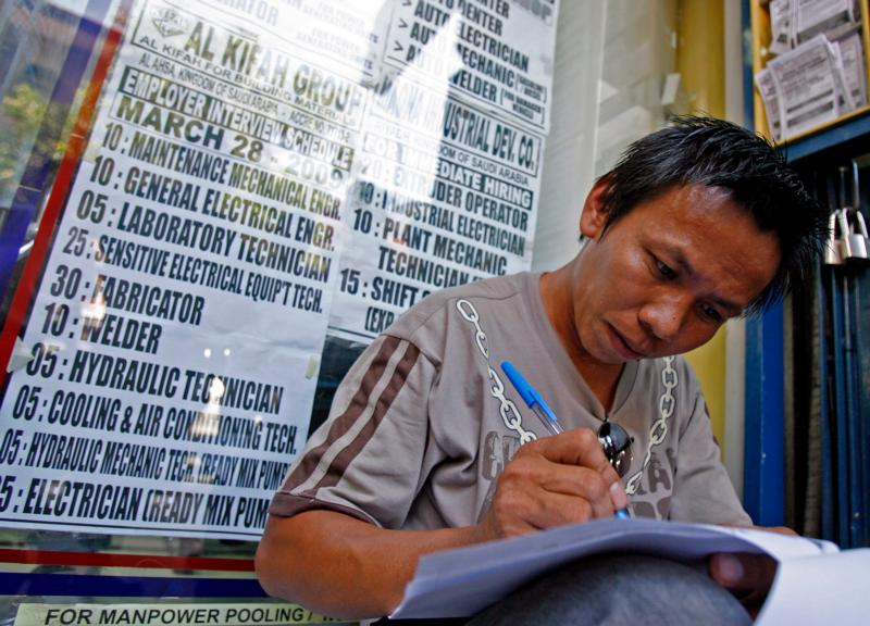 In this 2009 file photo, a Filipino jobseeker fills out forms outside a recruitment agency in Manila for jobs in the Middle East. Bishops there are preparing ways to support Filipinos working in the Middle East who might be affected by falling oil prices in the region. (CNS photo/Alanah Torralba, EPA)