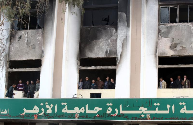 In this Dec. 29, 2013, file photo, Egyptian students look out the windows of a faculty building at Cairo's al-Azhar University one day after student supporters of the Muslim Brotherhood set it on fire in Cairo, Egypt. The Vatican's interreligious council invited Ahmad el-Tayeb, the grand imam of al-Azhar University, to travel to the Vatican and meet with Pope Francis. (CNS photo/Khaled Elfiqi, EPA)