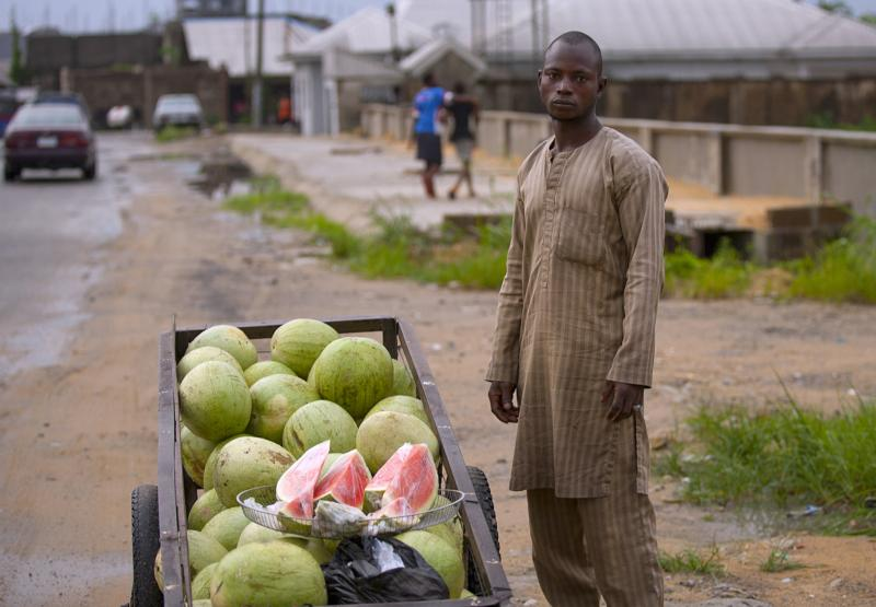In this April 22, 2015, file photo, a man sells watermelon slices on a roadside in Bayelsa, Nigeria. Nigeria's Catholic bishops called on the government to become less dependent on crude oil as the driver of the country's economy and to strengthen investments in grass-roots businesses to reduce glaring financial inequality. (CNS photo/Tife Owolabi, EPA)