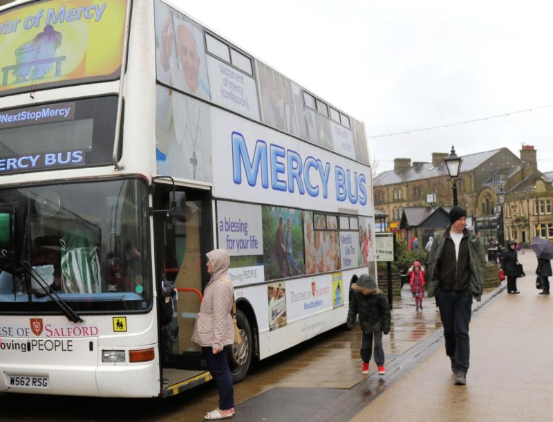 People walk by the Mercy Bus in Burnley, England, Feb. 20. The double-decker bus is used for priests to hear the confessions of people who have stopped going to church. (CNS photo/Simon Caldwell)