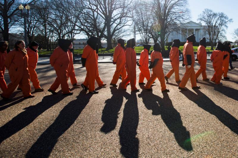 Activists dressed in orange jumpsuits representing detainees in the U.S.-run detention center at Guantanamo Bay, Cuba,  rally in front of the White House Jan. 11 asking President Barack Obama to close the facility and release or charge the dozens of men being held there. (CNS photo/Jim Lo Scalzo, EPA)
