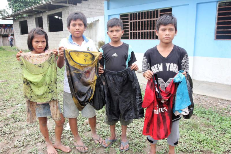 Awajun children in the community of Nazareth, at the confluence of the Chiriaco and Maranon rivers in northern Peru, show the clothes they wore -- with no protective equipment -- to scoop oil out of water near their community after a pipeline break. (CNS photo/Barbara Fraser)