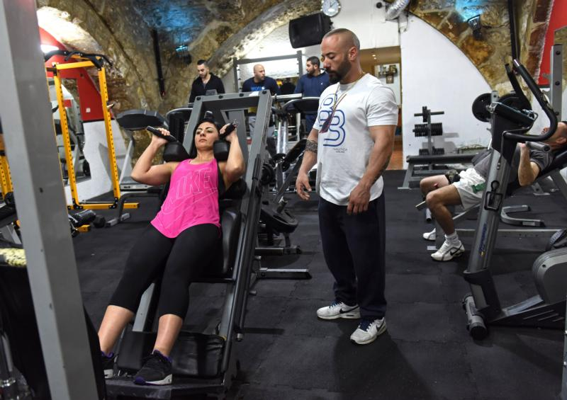 Anoush Belian of Jerusalem performs an exercise Feb. 8 while her trainer and nutritionist, Basel Said, looks on. Daughter of an Armenian Christian father and a Catholic Palestinian mother, Anoush is the first Palestinian or Armenian woman to take up the sport of bodybuilding and reach title level. (CNS photo/Debbie Hill)
