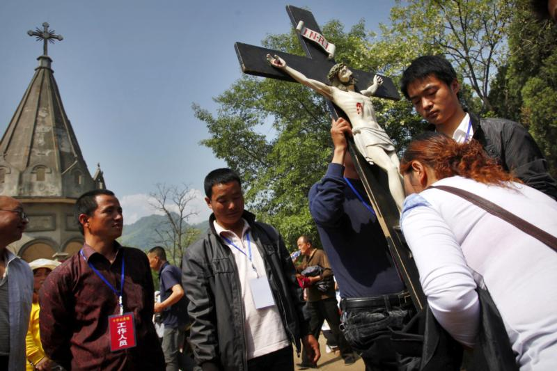 A Chinese Catholic kisses a crucifix during a pilgrimage in Baoji, China, in this May 3, 2013, file photo. Chinese authorities are continuing their campaign of removing crosses in Zhejiang province, and one of the latest was taken from a Catholic Church. (CNS photo/Wu Hong, EPA)