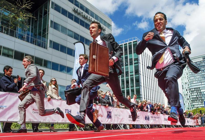 "In this May 20, 2015, file photo, contestants in the Netherlands compete in a charity race called ""Heels and Suits Run""  in Amsterdam. Pope Francis told business leaders not to let the mantra of economic freedom and thirst for profits prevail over human rights and freedoms. (CNS photo/Remko De Waal, EPA)"