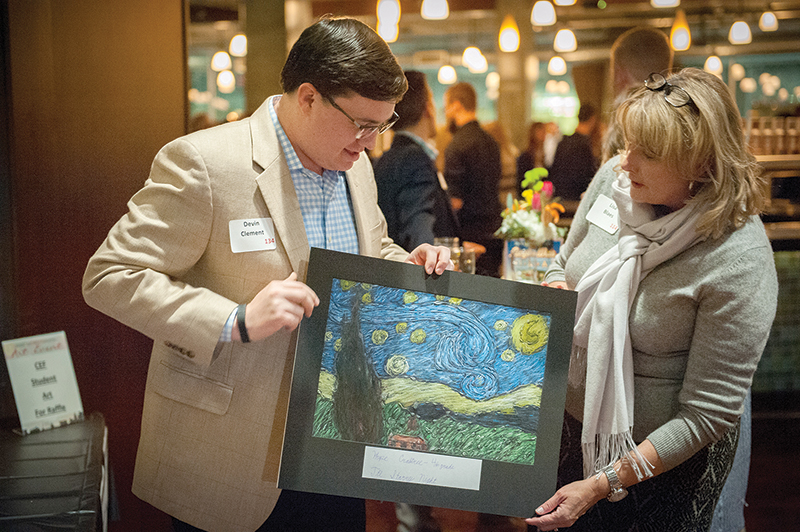 Devin Clement, a member of St. Joseph Parish in Shawnee, shows Lisa Blaes the artwork he won at the CEF Futures Art Event on Feb. 4. The art was done by a student at a CEF school. Leaven photo by Lori Wood Habiger