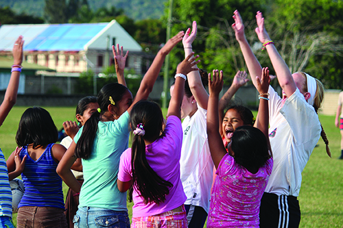 Photo by Ian Lee Student volunteers from Benedictine College in Atchison have fun with the children of Benque Viejo del Carmen, Belize. For 10 years, Benedictine students have dedicated their spring break to doing mission wor in the Benque community.