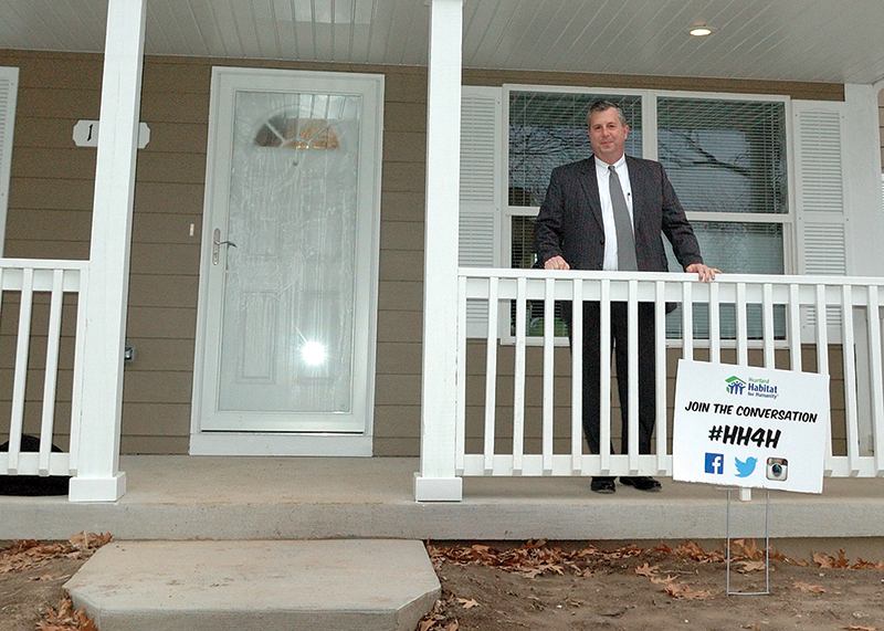 Heartland Habitat for Humanity president and CEO Tom Lally stands on the front porch of a recently completed Heartland Habitat for Humanity home that was blessed at the end of January.
