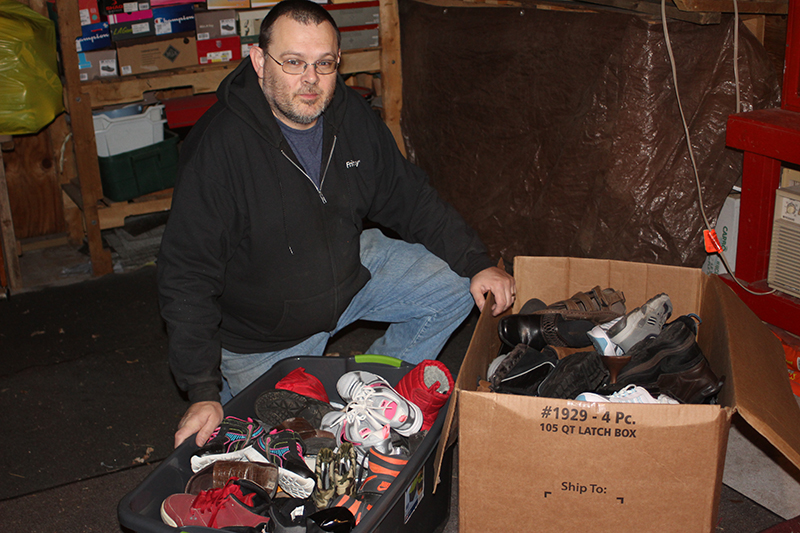 Jerry Hudgins, founder of Sole Reason, a ministry to distribute shoes to those in need, stands with some of the 1,000 pairs he's collected thus far. Hudgins plans to host the first distribution in early spring. Hudgins, a member of Topeka's Sacred Heart-St. Joseph Parish, got the idea from a high school student in Wichita's program. Leaven photo by Marc Anderson