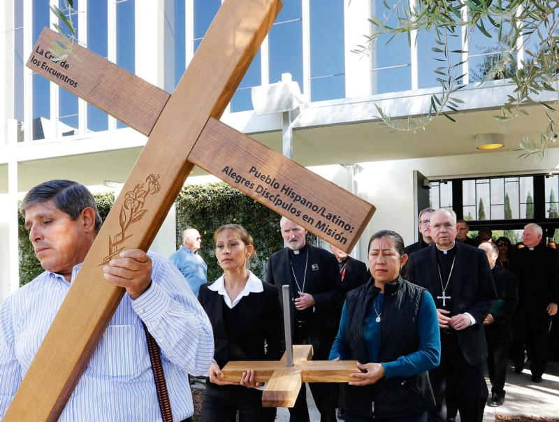 A man carries cross ahead of a Feb. 27 procession that includes Los Angeles Archbishop Jose H. Gomez, retired Auxiliary Bishop Dominic Luong of Orange, Calif., retired Auxiliary Bishop Rutilio del Riego of San Bernardino, Calif., and other Southern California bishops. The procession was part of the second annual Immigration Summit, which took place at Christ Cathedral in Garden Grove, Calif. (CNS photo/Victor Aleman)