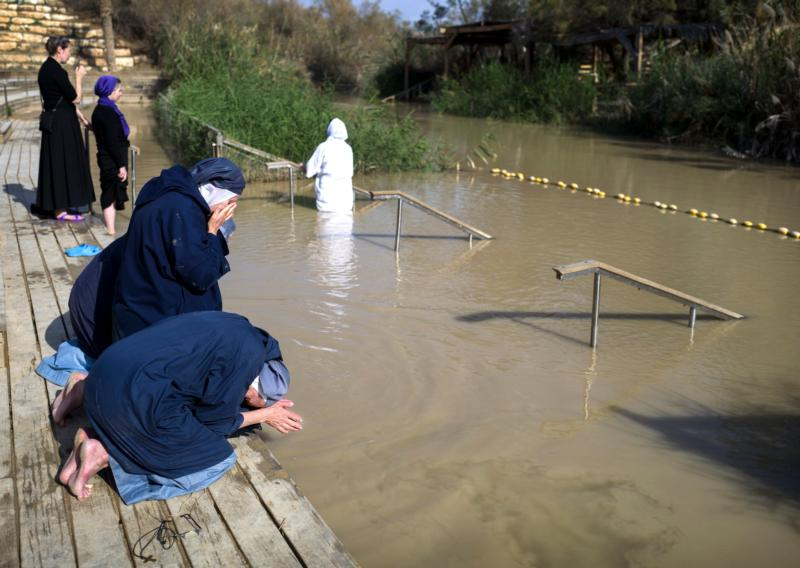 Women religious pray on the banks of the Jordan River, the river in which Jesus was baptized, in the West Bank Jan. 10. (CNS photo/Jim Hollander, EPA)