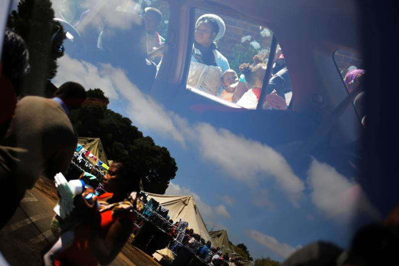 In this April 20, 2015, file photo, mothers and children are reflected in a vehicle window as they wait for food at a Red Cross refugee camp set up for foreign residents in Johannesburg, South Africa. South African bishops said South Africans need to have a candid conversation on racism. (CNS photo/Kim Ludbrook, EPA)