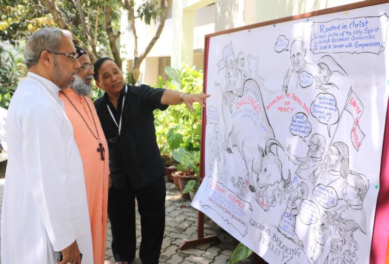 Bishop Stephen Rotluanga of Aizawl, India, explains his cartoon on the conference to Cardinal Baselios Cleemis Thottunkal in Bangalore March 9. (CNS photo/Anto Akkara)